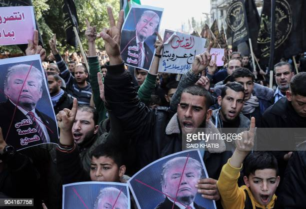 TOPSHOT Palestinian supporters of the Islamic Jihad movement shout slogans and hold up portraits of US President Donald Trump during a protest...