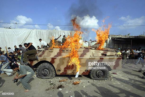 Palestinian supporters of the Islamic resistance Movement Hamas burn a Palestinian police tank during clashes as police attempt to prevent further...