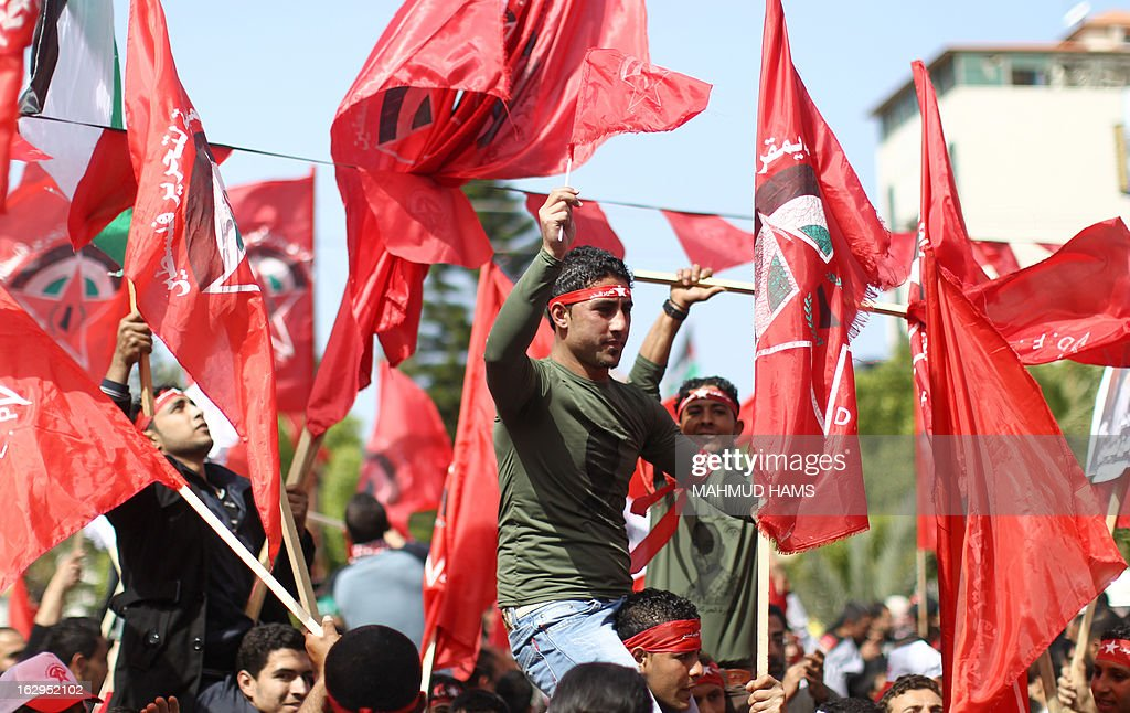 Palestinian supporters of the Popular Front for the Liberation of Palestine (PFLP), a Palestinian Marxist-Leninist and revolutionary leftist organization founded in 1967, wave the movement's red flag as they celebrate the 46th anniversary of its foundation in Gaza City, on March 2, 2013.