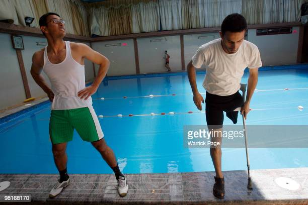 Palestinian swimmers, Abdul Rahman and Shahdi el-Masry perform warm-up stretches before training, at the Nama'a Sports Club, on March 30 in Jabaliya,...