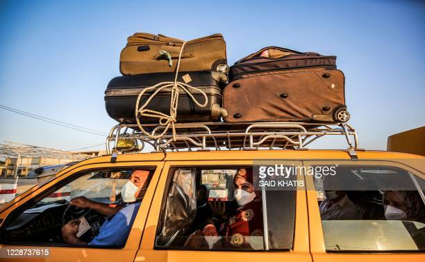 Palestinian taxi driver and passengers, mask-clad due to the COVID-19 coronavirus pandemic, wait in a vehicle as they wait to cross to the Egyptian...