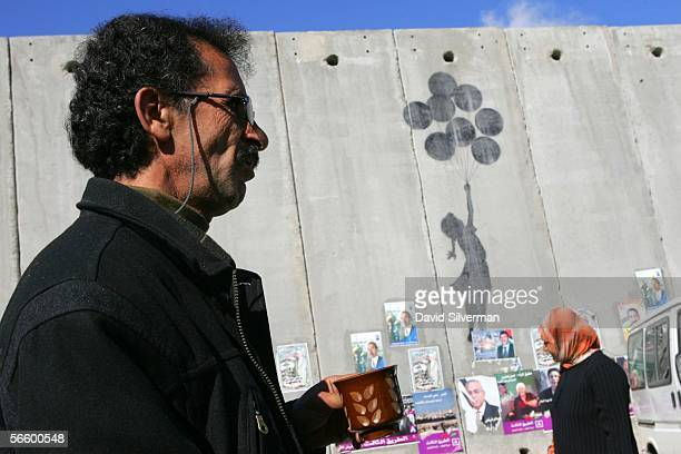 Palestinian taxi driver drinks his coffee as he waits for passengers alongside grafitti by the British artist Banksy on Israel's separation wall...