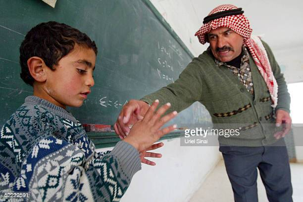 Palestinian teacher Ahmed Jubril does mathematics with one of his pupils at the regional school near the extremist Jewish settlement of Maon February...