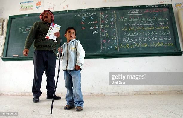 Palestinian teacher Ahmed Jubril stands in front of his class with one of his pupils at the regional school near the extremist Jewish settlement of...