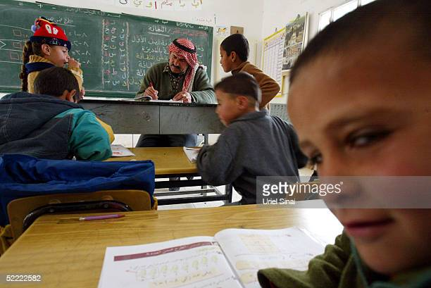 Palestinian teacher Ahmed Jubril teaches his class at the regional school near the extremist Jewish settlement of Maon February 20 2005 in the West...