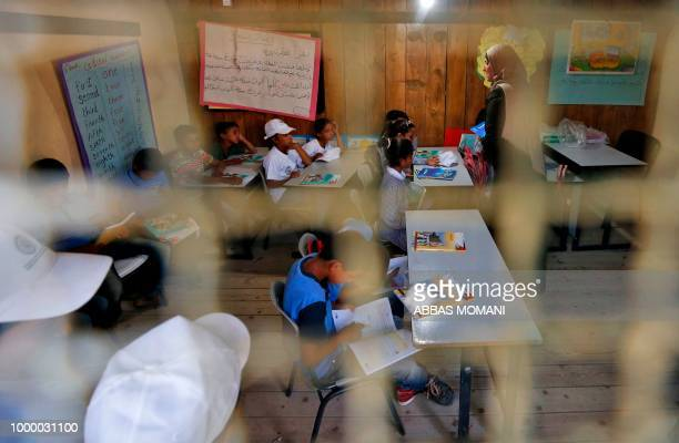 A Palestinian teacher talks to children in a classroom after the early start of classes at a school in the Bedouin village of Khan alAhmar in the...