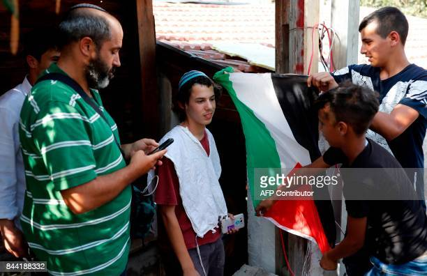 Palestinian teenagers display a Palestinian flag in front of religious Jewish settlers on September 8 during a protest outside a house seized by new...