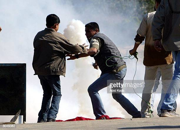 Palestinian throws a can of tear gas back at Israeli forces during clashes in the town near the Erez crossing on March 6 in Beit Hanoun Gaza Strip...