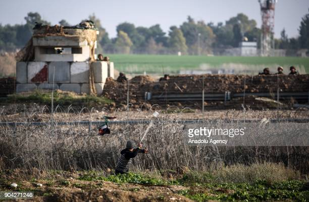 Palestinian throws a rock with a slingshot after Israeli security forces' intervention during a protest against US decision to recognize Jerusalem as...