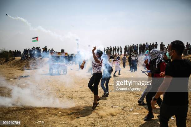 Palestinian throws back a tear gas can in response to Israel's intervention during Great March of Return at GazaIsrael border in Khan Yunis Gaza on...