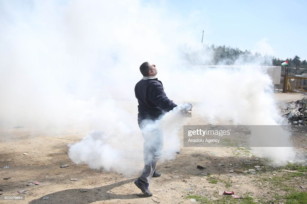A Palestinian throws back a tear gas can to Israeli security forces during a protest, organized by Palestine Committee Against the Wall and Settlements, which has connection with Palestine Liberation Organization, against Munzir Amira's detention at Ofer Prison located in west of Ramallah, West Bank on February 21, 2018.
