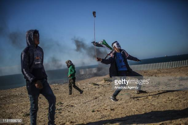 Palestinian throws stone with using a slingshot during Israeli forces' intervention within a maritime protest against Israels ongoing blockade of...