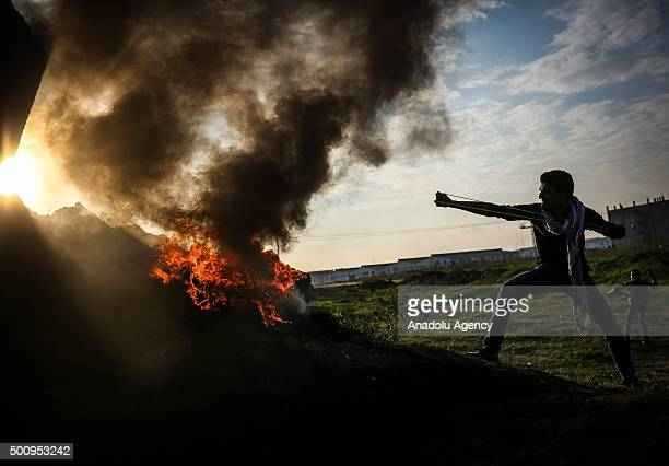 Palestinian throws stones at Israeli soldiers during a protest following the Friday prayers in the Shuja'iyya neighborhood on the IsraelGaza border...