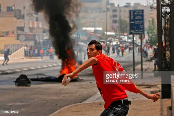 A Palestinian throws stones towards Israeli security forces during clashes after a protest marking the 70th anniversary of Nakba also known as Day of...