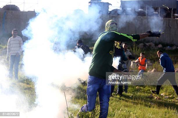 Palestinian throws tear gas back to Israeli security forces during a protest against the separation wall and Jewish settlement near the Ofer prison...