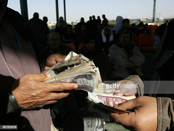 Palestinian traveler exchanges money as he waits to leave the Gaza Strip for Egypt at the Rafah border crossing November 23, 2005 in the southern...