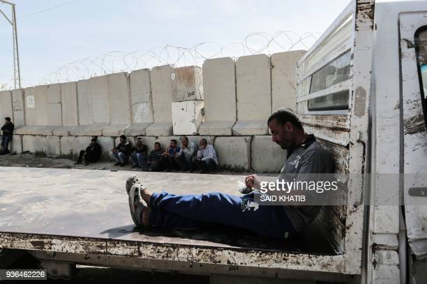 TOPSHOT Palestinian truck drivers sit with their lorries near the Kerem Shalom Crossing between the southern Gaza Strip and Israel on March 22 during...
