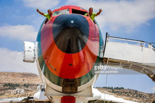Palestinian twin brothers Atallah and Khamis al-Sairafi pose from the cockpit of a Boeing 707 aircraft being converted into a restaurant they are...