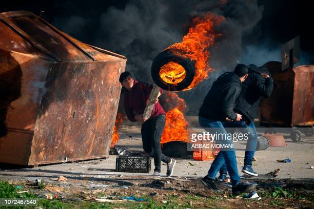 Palestinian uses a piece of wood to move a burning tire during clashes with Israeli troops in Ramallah near the Jewish settlement of Beit El in the...