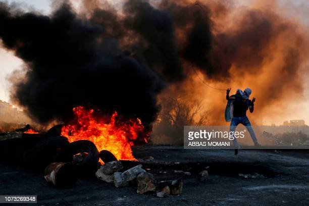 Palestinian uses a slingshot to hurl stones amid smoke during clashes with Israeli troops in Ramallah near the Jewish settlement of Beit El in the...