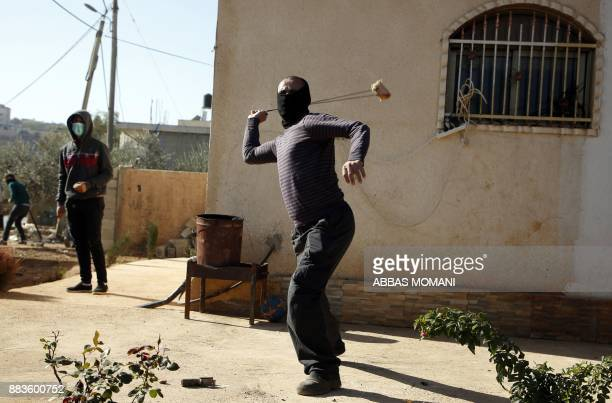 A Palestinian uses a slingshot to throw stones at Israeli soldiers during clashes in the northern village of Qusra in the occupied West Bank near...