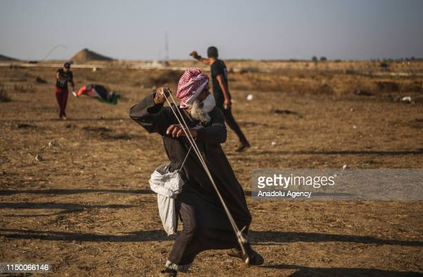 "Palestinian uses slingshot to throw stones towards Israeli security forces during a demonstration within the ""Great March of Return"" at Israel-Gaza..."
