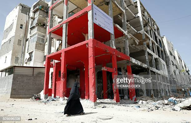 Palestinian veiled woman walks past a building which was destroyed during the 50day war between Israel and Hamasled militants in the summer of 2014...