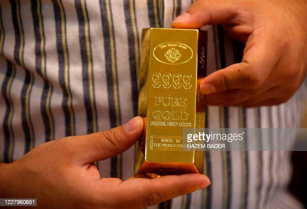 A Palestinian vendor displays a gold ingot amid soaring prices for this commodity at a jewelry shop in the city of Hebron in the occupied West Bank...