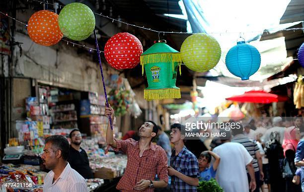 A Palestinian vendor displays traditional lanterns known in Arabic as 'Fanous' sold during the Muslim holy month of Ramadan at a market in Gaza City...