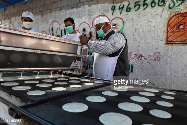 A Palestinian vendor makes Ramadan traditional sweets during the holy fasting month of Ramadan amid concerns about the spread of the coronavirus...