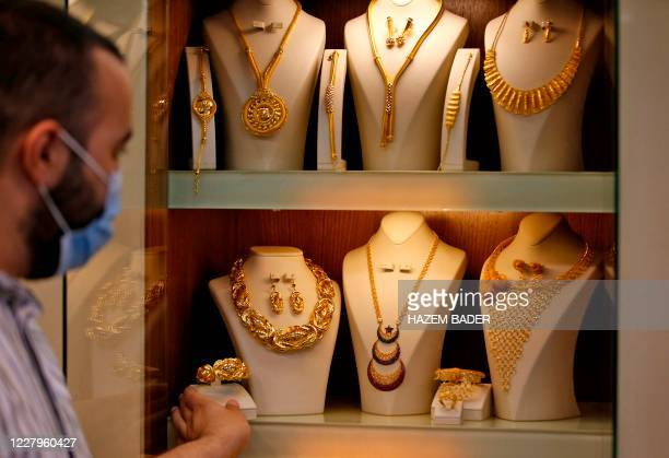 A Palestinian vendor picks a bracelet from a display at his jewelry shop amid soaring gold prices in the city of Hebron in the occupied West Bank on...