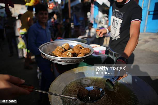 Palestinian vendor prepares traditional pancakes known as ''Falafel''' in a street market on the fifth day of the holy month of Ramadan in Rafah in...