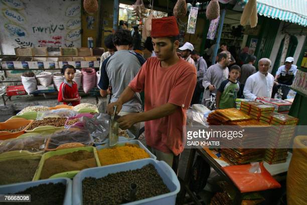 Palestinian vendor serves a client at a market in the town of Khan Yunis, southern Gaza Strip, ahead of the holy month of Ramadan, 11 September 2007....