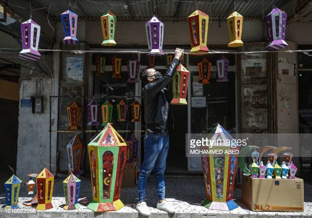 Palestinian vendor wearing a protective mask displays Ramadan lanterns for sale outside his shop in Gaza City on April 15 as Muslims across the world...