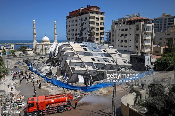 Palestinian volunteers and municipal workers clear the rubble of buildings, recently destroyed by Israeli strikes, in Gaza City's Rimal district on...