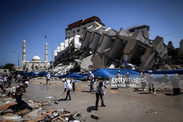 Palestinian volunteers and municipal workers clear the rubble of the Hanadi compound, recently destroyed by Israeli strikes, in Gaza City's Rimal...