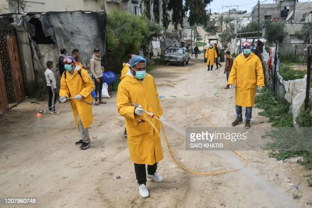 Palestinian volunteers wearing protective clothes and masks disinfect a street as a preventive measure against the spread of the novel coronavirus in...