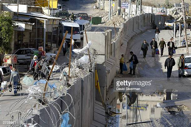 Palestinian walk on both the Israeli and West Bank sides of Israel's graffiticovered separation wall November 13 2003 which cuts through the Arab...