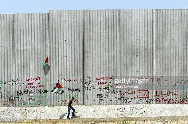 "Palestinian walks alongside Israel""s security wall July 31, 2003 during a protest against the 8-meter high barrier that flanks the West Bank..."