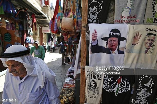 A Palestinian walks past a souvenir shop displaying Tshirts bearing images of US President Barack Obama wearing a kaffiyeh and presidentelect Donald...