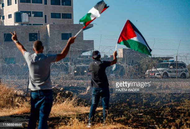 Palestinian wave the national flags during clashes with Israeli forces following a demonstration against an Israeli court issued demolition notice of...