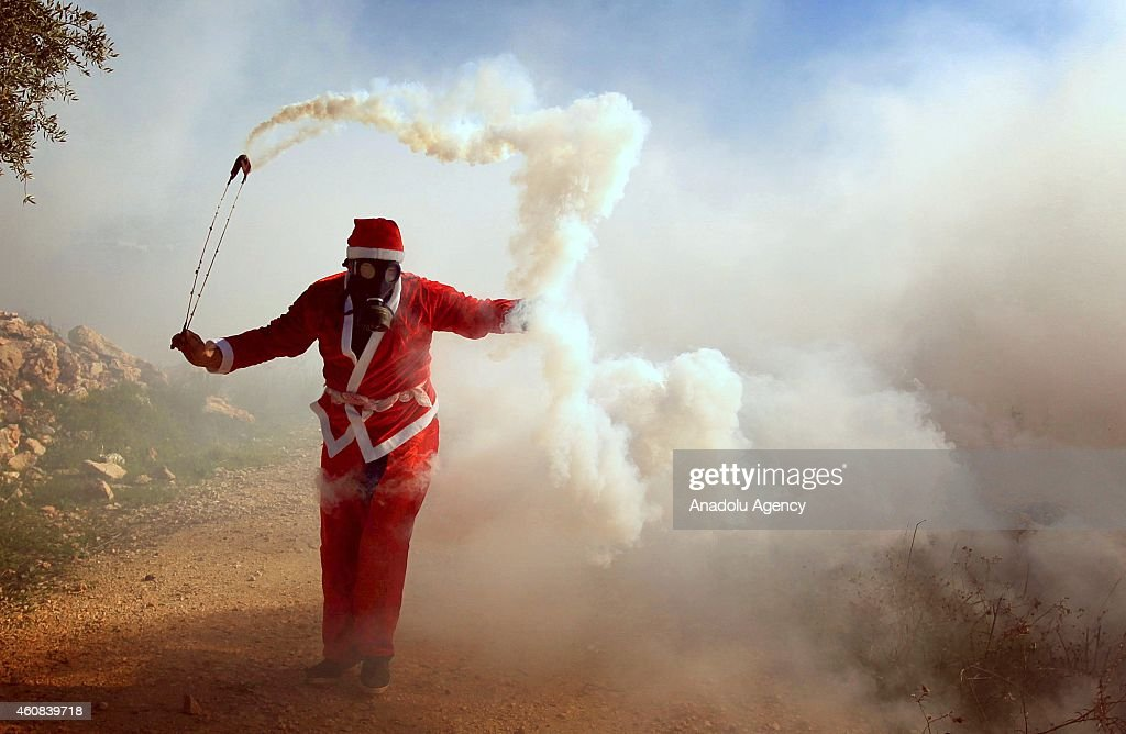 A Palestinian, wears a Santa Clause costume, throws a tear gas capsule back to the Israeli security forces during a protest against the separation barrier (wall) and Jewish settlement construction at Bilin Village, in Ramallah, West Bank on December 26, 2014.