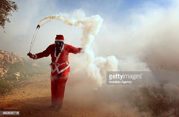 Palestinian wears a Santa Clause costume throws a tear gas capsule back to the Israeli security forces during a protest against the separation...