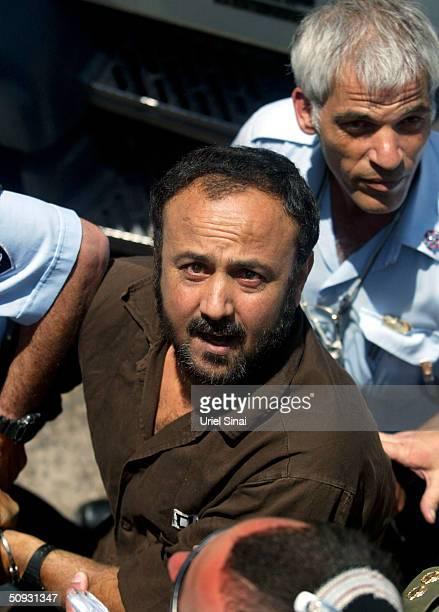 Palestinian West Bank Fatah leader Marwan Barghuti flanked by Israeli guards arrives at a Tel Aviv court June 6 2004 in Israel Barghuti considered...