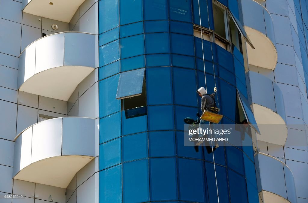 A Palestinian window cleaner works at the al-Zafer building in Gaza City on March 14, 2017. /