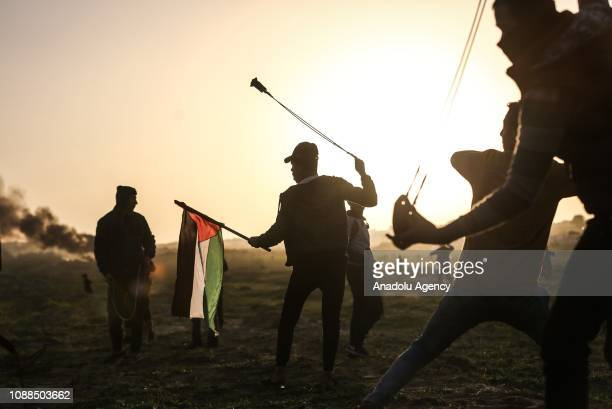 Palestinian with a Palestinian flag throws a stone with a slingshot in response to Israeli forces' intervention during Great March of Return...