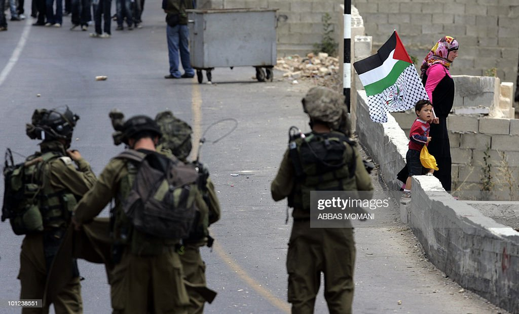 A Palestinian woman and a child holding their national and the Fatah party flag walk between Israeli forces and Palestinian demonstrators (top) during a protest against Israeli settlements expansion and occupation in the West Bank village of Nabi Saleh on May 28, 2010.