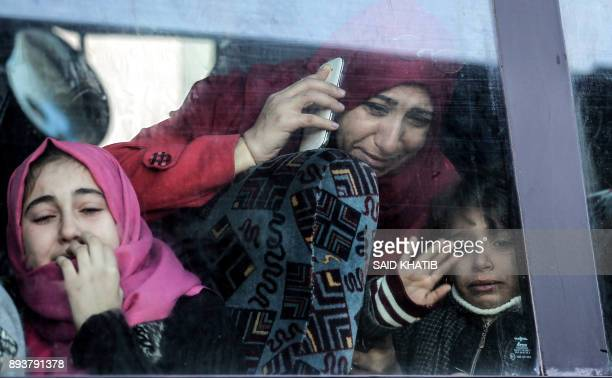 Palestinian woman and child bid farewell through the window of a bus in Khan Younis in the southern Gaza strip on December 16, 2017 prior to their...