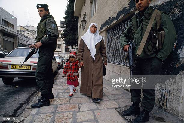 A Palestinian woman and girl walk past a military checkpoint in the Occupied Territories in East Jerusalem Israel began its seizure and settlement of...
