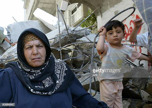 Palestinian woman and her child sit amid the rubble of their destroyed house at Tel alSultan neighbourhood in the southern Gaza Strip refugee camp of...
